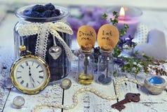 De uitstekende voorwerpen, uiterst kleine flessen met etiketten eten me en drinken me, oude klokken, sleutel en honingsbes in kru Royalty-vrije Stock Afbeelding