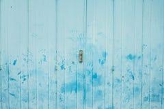 De uitstekende vouwende metaaldeur met de lichtblauwe geschilderde en vlek van de handdruk stock fotografie