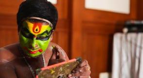 De uitvoerder die van de Katakhalidans gezichtsverf en make-up voor hand doen - gehouden spiegel stock afbeelding