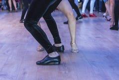 De uitvoerders van de Salsadans op een dansvloer, binnen, voeten details, sluiten omhoog stock foto