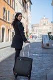 De uitvoerende en moderne vrouw loopt de straat met haar bagage en Stock Foto's