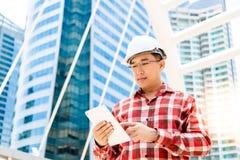 De uitvoerende ingenieurskerel gebruikt tablet voor verslag zijn werk of Sc stock afbeelding