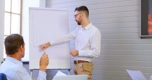 De uitvoerende macht die over whiteboard in conferentieruimte 4k bespreken stock video