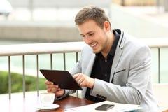De uitvoerende werken met een tablet in een koffiewinkel Stock Fotografie