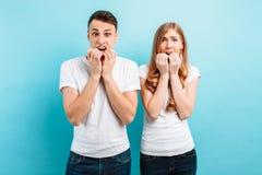 De um par novo, homem amedrontado e mulher, guardando as mãos perto da boca, expressões amedrontadas, em um fundo azul imagens de stock royalty free