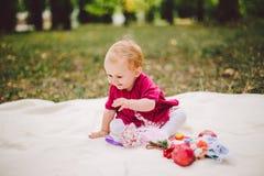 De un año rubio de la pequeña pertenencia étnica caucásica del bebé de nacimiento se sienta en una tela escocesa en hierba verde  fotografía de archivo libre de regalías