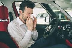 De un hombre joven con el pañuelo El individuo enfermo tiene mocos el hombre hace una curación para el frío común en el coche Imagenes de archivo