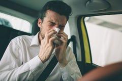 De un hombre joven con el pañuelo El individuo enfermo tiene mocos el hombre hace una curación para el frío común en el coche Fotografía de archivo libre de regalías