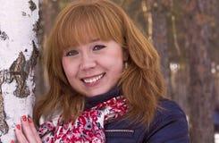 De una muchacha pelirroja alegre en el parque entre abedules Foto de archivo libre de regalías