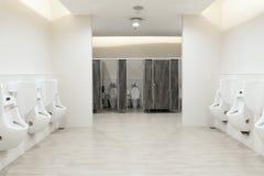 De urinoirs van de mensen` s ruimte lossen, Toiletkom in een moderne badkamers met bakken en toiletpapier Royalty-vrije Stock Foto's