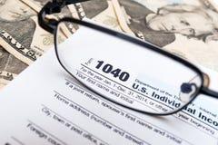 De V.S. 1040 de individuele close-up van de belastingaangiftevorm met glazen en dollarrekeningen Royalty-vrije Stock Afbeelding