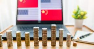 De V.S. versus de vlag van China in laptop het scherm op houten lijst De gouden en zilveren muntstukken zijn voor van laptop en n royalty-vrije stock fotografie