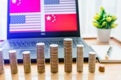 De V.S. versus de vlag van China in laptop het scherm op houten lijst De gouden en zilveren muntstukken zijn voor van laptop en n royalty-vrije stock foto