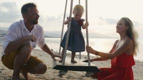 De vader bevordert dochter het slingeren op de schommeling stock videobeelden