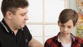 De vader controleert zijn tienerzoon hometask in een voorbeeldenboek dicht omhoog langzame motie bekijkt stock video