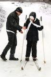 De vader, de dochter en de skis. Stock Foto's