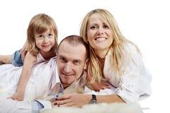 De vader, de moeder en de dochter liggen op tapijt Stock Afbeeldingen