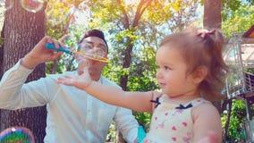 De vader die zeepbels blazen en weinig dochter vangt hen in het park, het concept van de levensstijlfamilie stock video