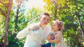 De vader die zeepbels blazen en weinig dochter vangt hen in het park, het concept van de levensstijlfamilie stock footage