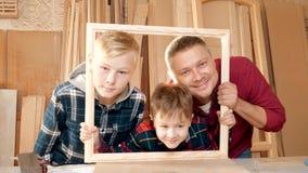 De vader is een zoon van de timmermans` s workshop Vriendschappelijke familie binnen, grappig portret stock footage
