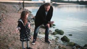 De vader en de dochter op de kust, meisje werpen steen in het water De mens toont aan meisje hoe spelsteen het overslaan stock videobeelden