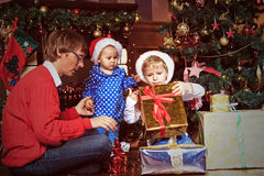 De vader en de jonge geitjes met stellen in Kerstmis voor Stock Afbeeldingen