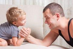 De vader en de jonge zoon vechten Stock Foto's