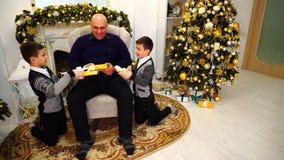 De vader en de kinderen met tweelingjongens ruilen giften en lach in woonkamer met open haard en lange Kerstboom stock videobeelden