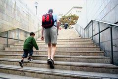 De vader en de zoon beklimmen treden Stock Foto's