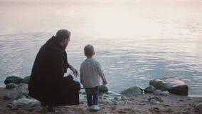 De vader en de zoon op de kust, weinig jongen werpen steen in het water De mens die en toont jongen hoe spelsteen het overslaan h stock footage