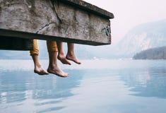 De vader en de zoon slingerden hun benen van de houten pijler op berg stock foto's
