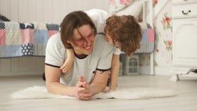 De vader en de zoon spelen op de vloer in de slaapkamer stock videobeelden