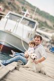De vader en de zoon zitten met honden op een bank dichtbij het overzees Royalty-vrije Stock Afbeelding