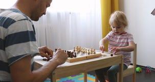 De vader en de dochter het spelen van hersenenspelen schaak thuis stock footage