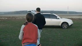 De vader en de dochter verzamelen draagstoel, een mand, gaan naar de auto Zij gaan na een picknick weggaan stock video