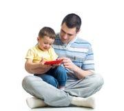 De vader en het jonge geitje zien eruit om tabletcomputer te spelen en te lezen Stock Foto's
