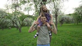 De vader en het kind genieten van het leven Mens met meisje op schouders Handbediend schot stock video