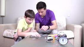 De vader en het kind maken raadsel stock video