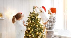 De vader en de kinderen die van de familiemoeder een Kerstboom verfraaien bij Royalty-vrije Stock Fotografie