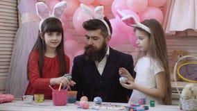 De vader en twee dochters verfraaien en schilderen paaseieren Gelukkige familie die voor Pasen voorbereidingen treffen Het leuke  stock video