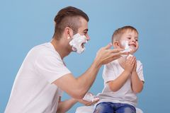 De vader en weinig zoon hebben pret samen, vader met schuim voor het scheren, smeren zijn zoons` s gezicht met het scheren van sc stock fotografie