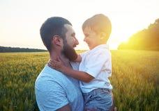 De vader en zijn kleine zoon bekijken elkaar tijdens zonsondergang Stock Afbeelding