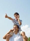 De vader en zijn zoon spreken over mobiles stock afbeelding