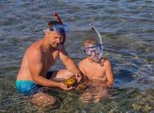 De vader en de zonduiker vinden twee grote shells in het Egeïsche overzees Stock Afbeeldingen