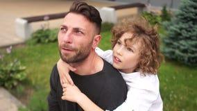 De vader en de zoon bekijken de hemel Een jonge mens met zijn zoon heeft pret in het park Gelukkig familieweekend stock videobeelden