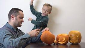 De vader en de zoon bereiden Halloween-pompoenen, speels kind voor stock videobeelden