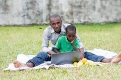 De vader en de zoon kijken samen op laptop royalty-vrije stock afbeelding