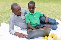 De vader en de zoon kijken samen op laptop stock foto
