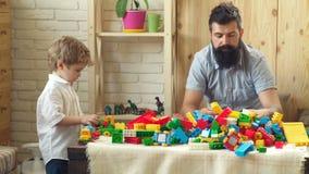 De vader en de zoon met gelukkige gezichten creëren kleurrijke bouw met stuk speelgoed bakstenen De jongen en zijn vader spelen m stock videobeelden