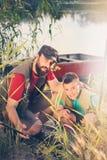 de vader en de zoon samen bij de visserij, bereiden vistuigen voor die aan de boot zullen worden genomen stock fotografie